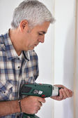 Grey- haired man drilling hole in wall — Stock Photo