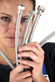Woman with metal flexible hoses — Stock Photo