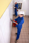 Top view of electricians in a tiled room — Stock Photo