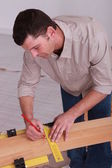 Man measuring wooden plank — Stock Photo