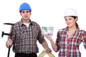 A team of tradespeople holding their tools and a house model — Stock Photo