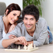 Couple laying on floor playing chess — Stock Photo