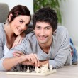 Stock Photo: Couple laying on floor playing chess