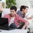 Couple relaxing on sofa with laptop and book — Stock Photo