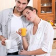 Couple in kitchen with coffee and orange juice — Stock Photo