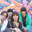 Group of teenagers sitting in front of a graffiti wall — Stock Photo