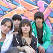 Group of teenagers sitting in front of graffiti wall — Stock Photo #8797598