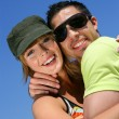 Couple hugging against a blue sky - Stockfoto