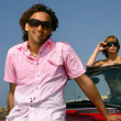 Stock Photo: Guy showing off near roadster with pretty girl