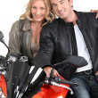 Stock Photo: Biker chic with arms around biker.