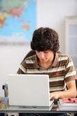 Teenager using his laptop at school — Stock Photo