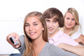 Three teenagers watching television together — Stock Photo