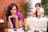 Angry woman at the restaurant, on the table, an unopened gift and flutes o — Stock Photo
