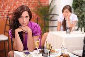 Mujer enojada en el restaurante, en la mesa, un regalo sin abrir y flautas o — Foto de Stock