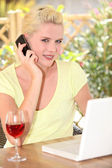 Woman talking on her mobile phone in front of her laptop and a glass of win — Stock Photo