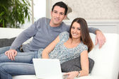 Duo lying on sofa with laptop — Stock Photo