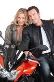 Biker chic with arms around biker. — Stockfoto