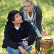 Stock Photo: Young couple gathering mushrooms in field