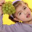 Little girl eating grapes - Stock Photo