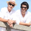 Two men in white leaning on a fence with a blue sky background — Stock Photo #8803087