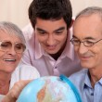 Family gathered around globe — Stock Photo