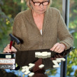 Old woman playing dominos — Stock Photo