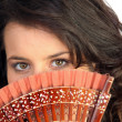 Closeup of a pretty woman hiding behind a fan - Stock Photo