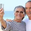 Older couple taking their own photograph at the beach — Stock Photo