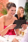 Woman looking at the menu at a restaurant — Stock Photo