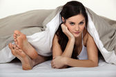 Annoyed woman in bed next to her partner's feet — Stock Photo