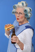 Funny picture of grandma with hair curlers relishing cheeseburger with beer — Stock Photo