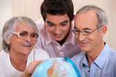 Family gathered around globe — Stock Photo