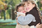 Young girls hugging outside — Stock Photo