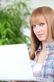 Red haired girl with laptop — Stock Photo