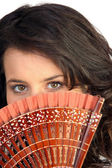 Closeup of a pretty woman hiding behind a fan — Stock Photo