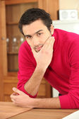 Young dark-haired guy in kitchen wearing raspberry red jumper — Stock Photo