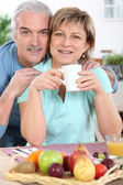 Mature couple all smiles at breakfast — Stock Photo