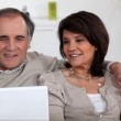 Mature couple sitting on sofa with laptop — Stock Photo #8810402