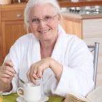 Granny in the kitchen having breakfast — Stock Photo