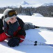 Male skier laying down in snow - Foto Stock