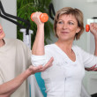 Foto Stock: Mature womworking out with personal trainer