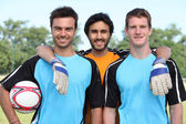 Three smiling footballers with ball — Stock Photo