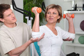 Mature woman working out with a personal trainer — Stock Photo