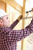 Builder using a clamp to fix two planks of wood together — Stock Photo