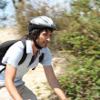 Action shot of man riding bike through forest — Stock Photo #8836782