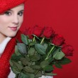 A cute blond holding a bunch of roses. — Stock Photo