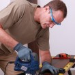 Man using an electric saw to cut a wooden floorboard — Stock Photo