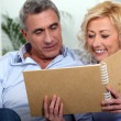 Smiling man and woman watching a photo album - Stock Photo