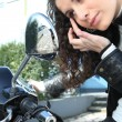 Woman applying eye make-up with the help of her motorcycle's mirror - Stok fotoğraf