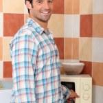 Man heating food in microwave — Stock Photo #8837424